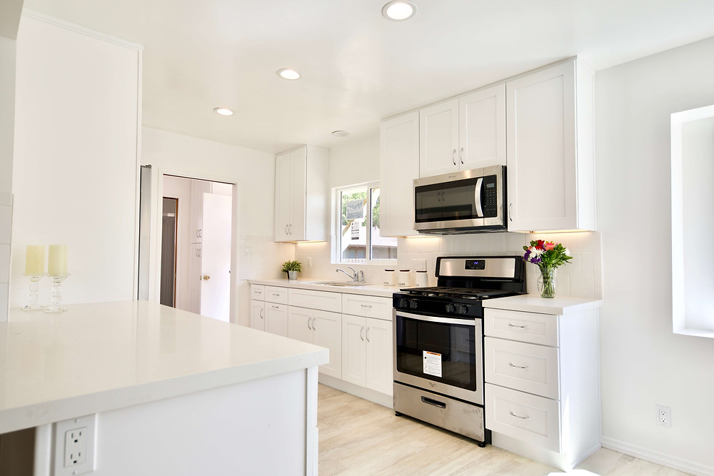 a white galley kitchen with stainless steel appliances