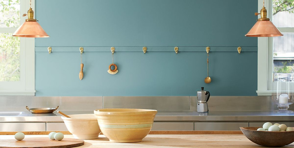 Aegean teal paint color on a kitchen wall with copper lighting, mixing bowls and other baking goods on the counter