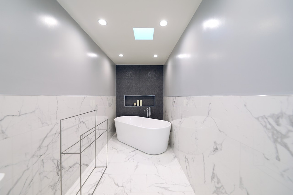 Black, white and gray bathroom with marble-inspired quartz and a skylight