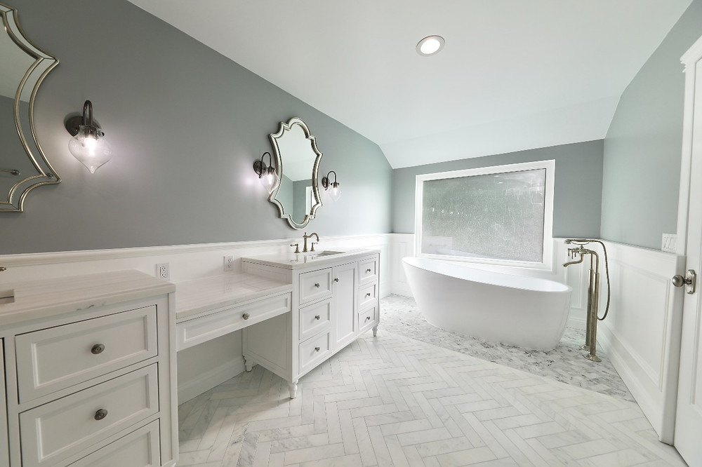 a white marble bathroom with herringbone tile a double vanity, built-in makeup counter and soaking tub under a large window