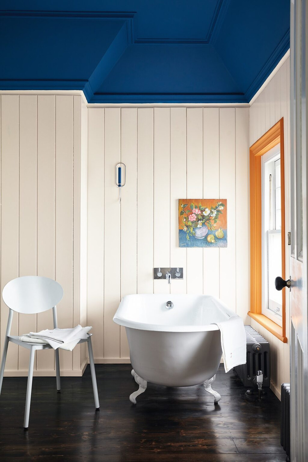 bathroom with blue painted ceiling and window trim painted orange