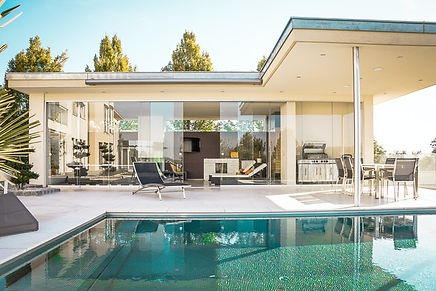 a modern adu with a glass front, pool and patio