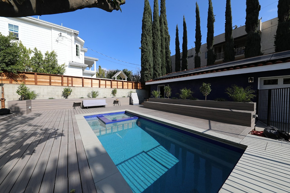 inground pool and spa with plank deck surrounding it