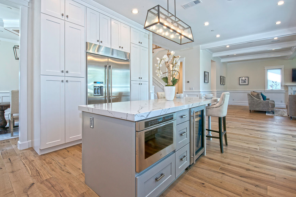 a luxurious on-trend kitchen remodel is an island that has thick countertop edges and gray cabinets