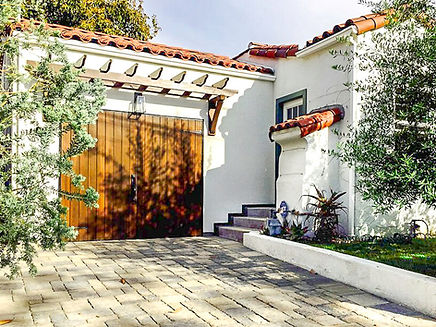 a white spanish style garage with a wooden door