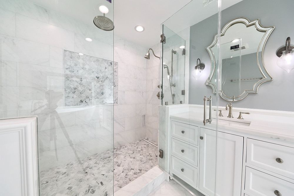 a luxurious on-trend white marble and gray bathroom with large rain shower
