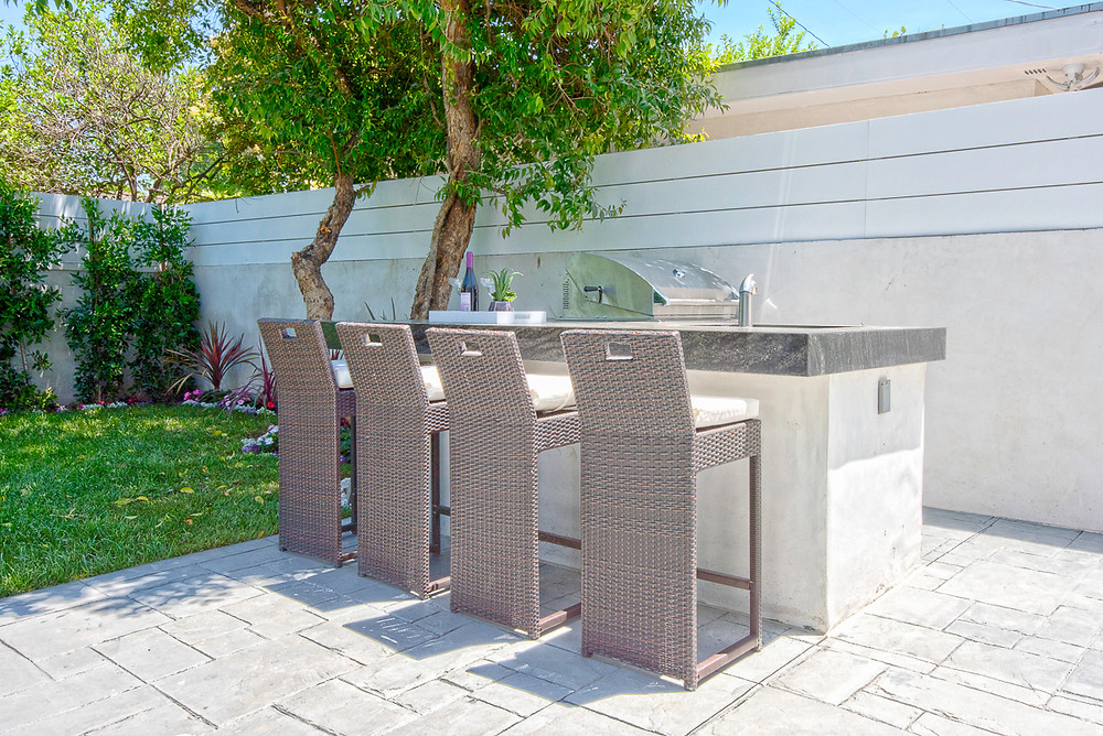 a built-in outdoor kitchen with a grill, bar seating and mini fridge