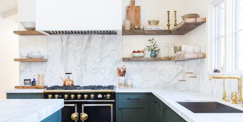 a dark blue and white kitchen with wooden open shelving and gold hardware