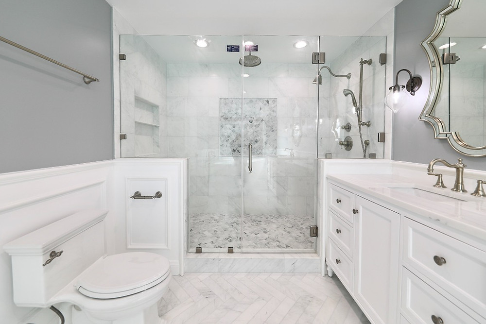 A large bathroom with white marble tile and a white quartz vanity
