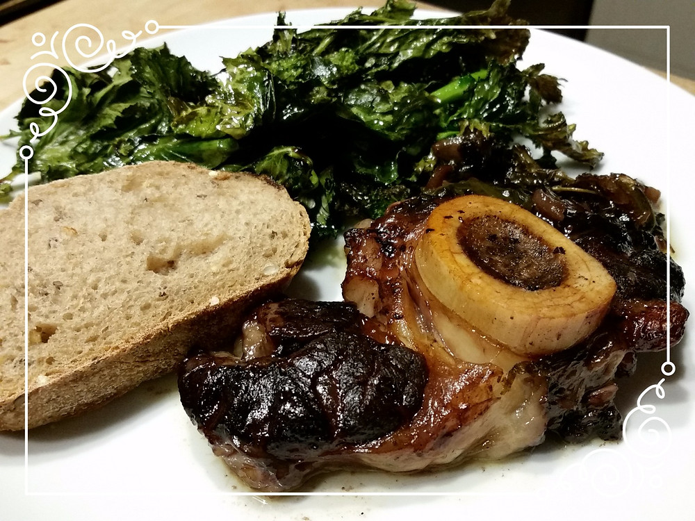 Finished braised shank with bread and roasted broccoli rabe.