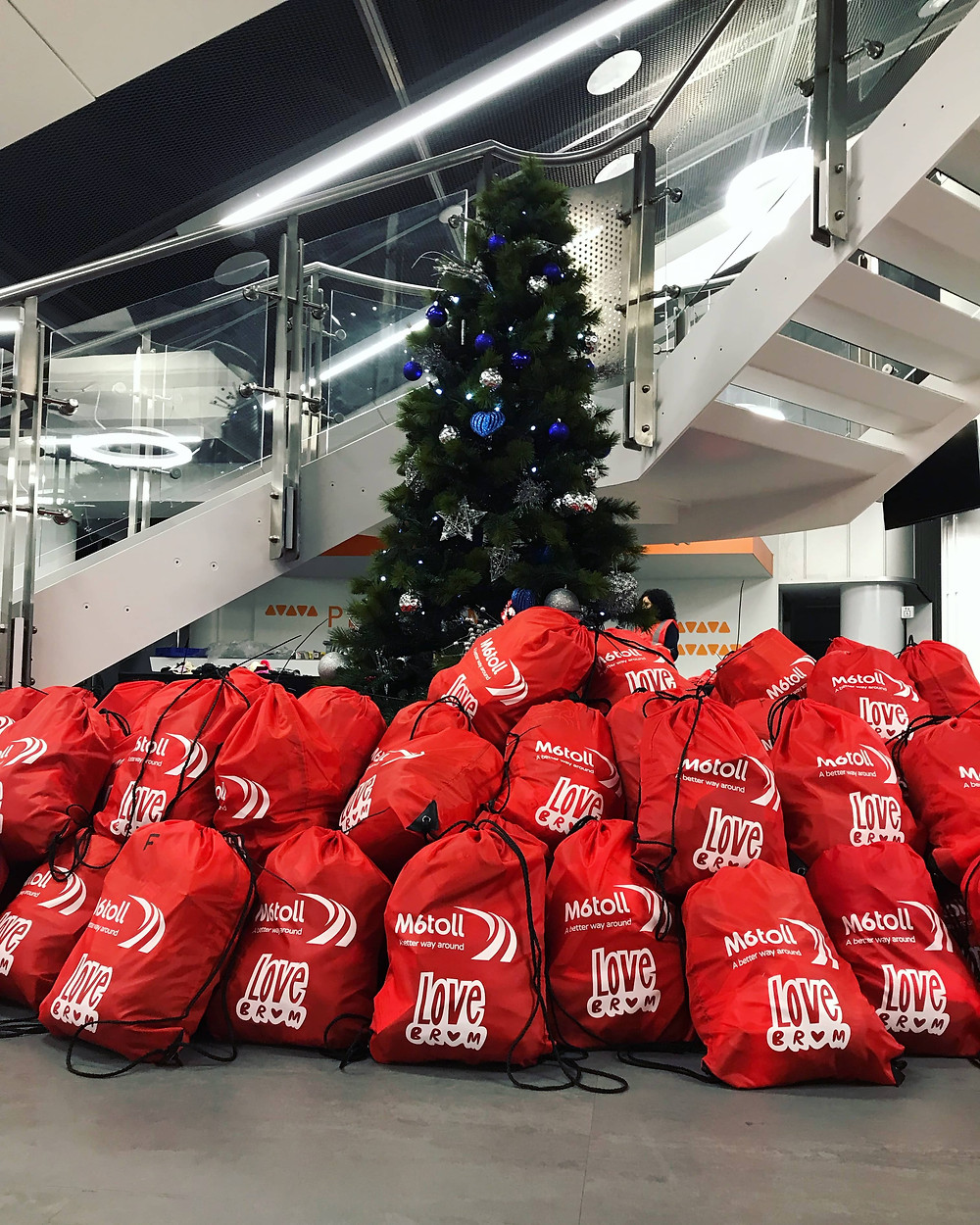 A large pile of bags sit in front of a christmas tree, filled with essential items for Birmingham's homeless. They are branded with the LoveBrum logo
