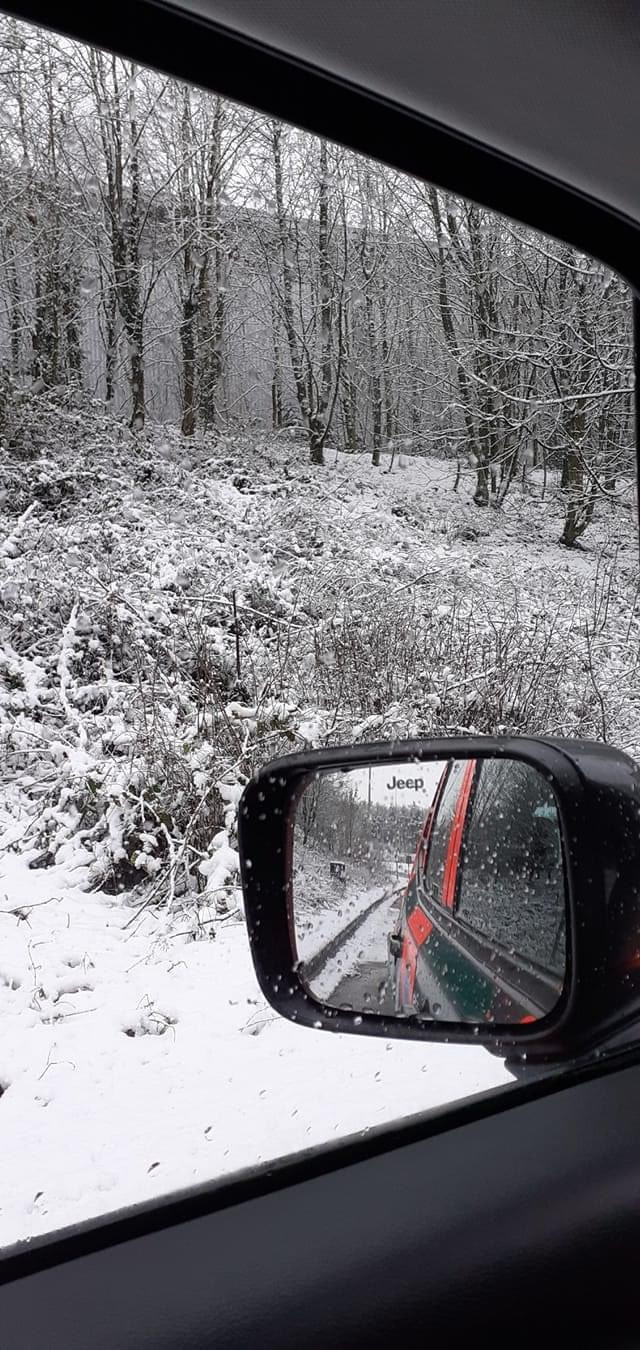 A picture out of the window of a first responder's car, showing a snowy woodland and road.