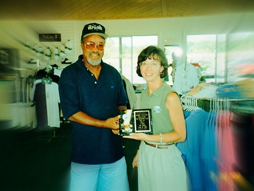 Mary Carter presents the Hole-in-One award to Jim Cleaves at the Mackinaw Club golf course in Mackinaw City, MI.