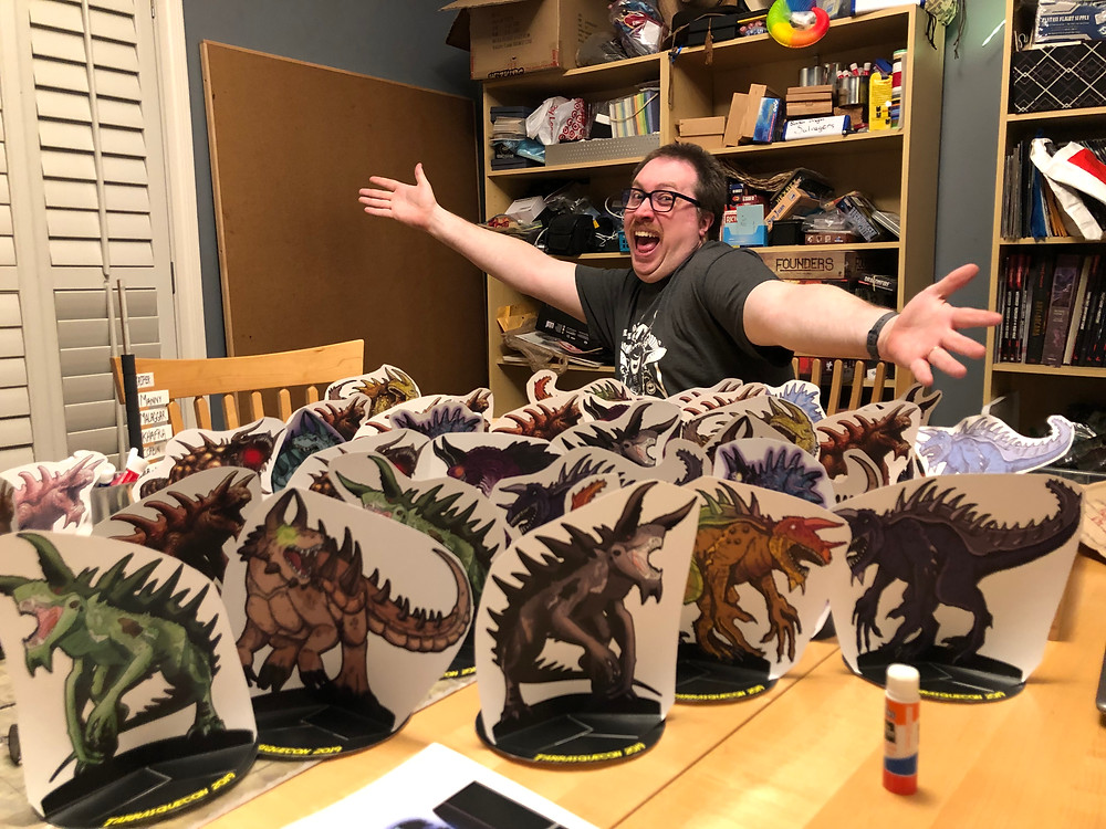 Ben Heisler with a maniacal grin showing off about seventy paper miniatures of tarrasques.
