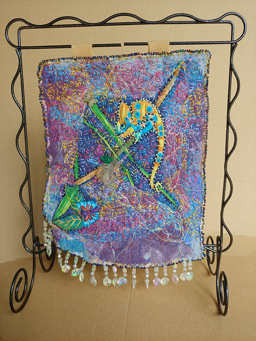 The ChameleonArt Quilt  Background of dryer lint on felt, covered with tulle, heavily embroidered by hand and beaded.