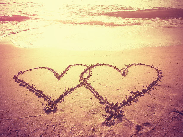 Vintage style photo of two hearts shape draw on the sand of a beach in morning time.jpg Concept for