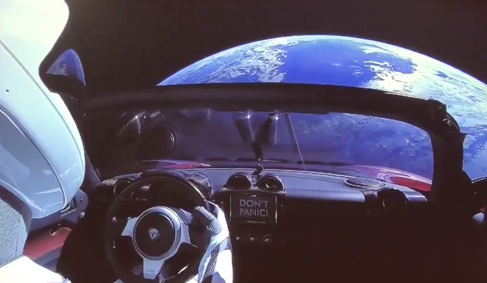 Elon Musk's Tesla Roadster floating above the Earth in Space.