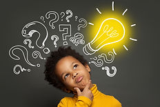 Thinking child boy on black background with light bulb and question marks. Brainstorming a