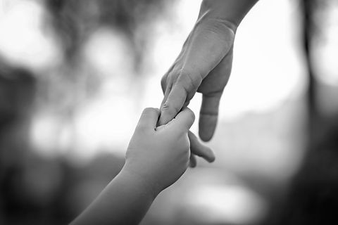 Parent holds the hand of a little child