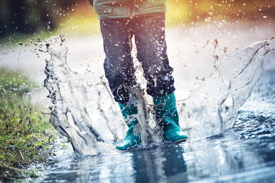 Child walking in wellies in puddle on ra