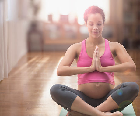 Pregnant mixed race woman meditating on yoga ma