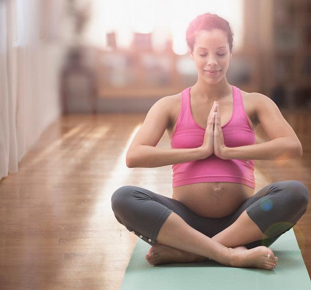 Pregnant mixed race woman meditating on yoga ma