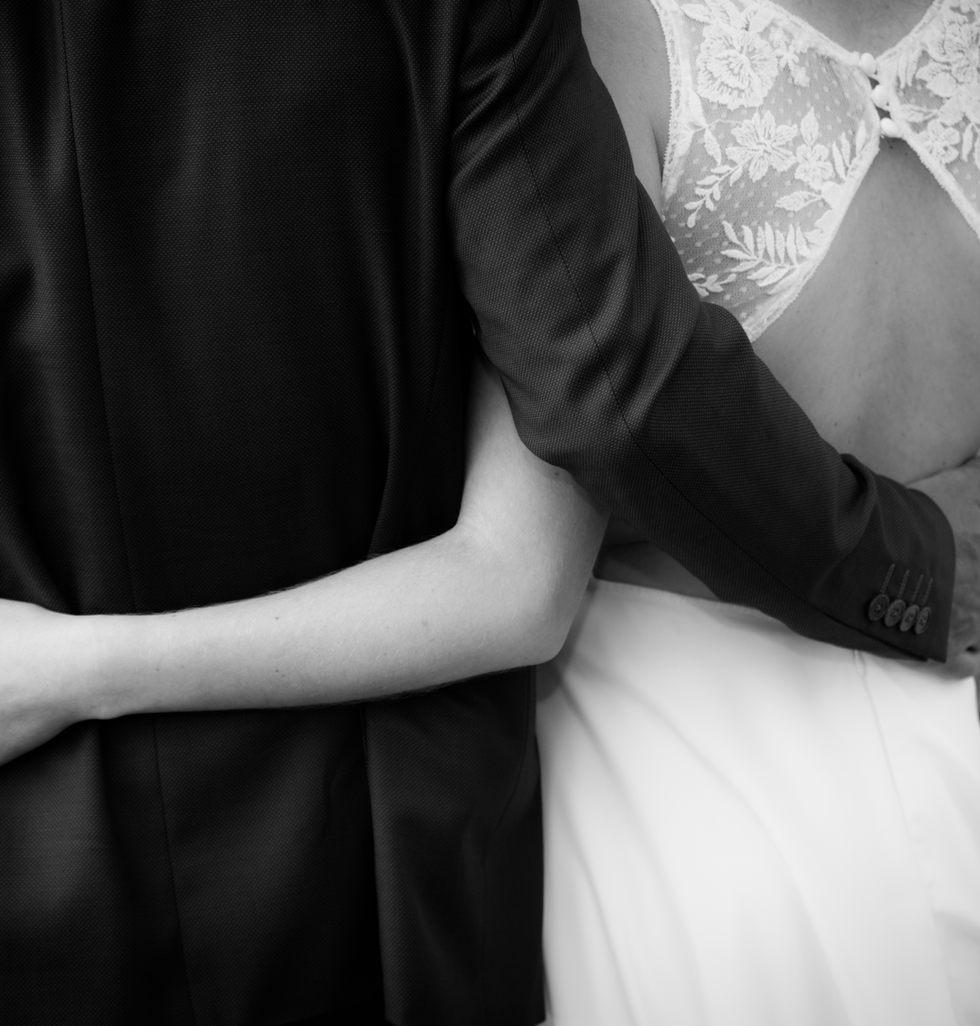 dos des mariés et leurs bras se serrent