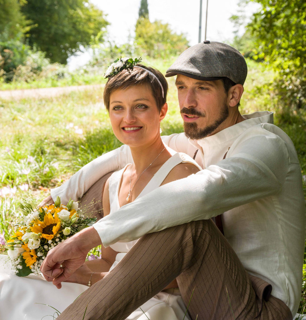 les mariés assis dans l'herbe