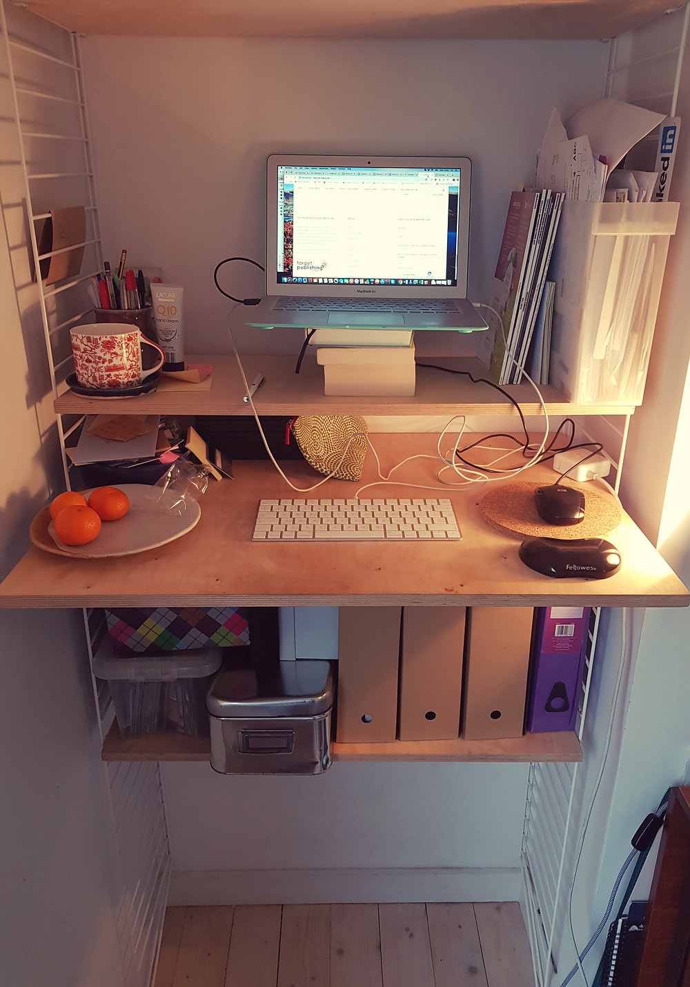 My new standing desk, complete with clementines and biscuit wrappers