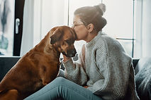Woman cuddles, plays with her dog at hom