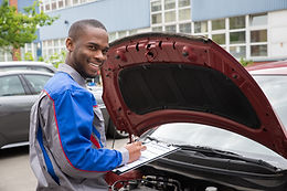 mechanic-with-clipboard-in-front-of-a-ca