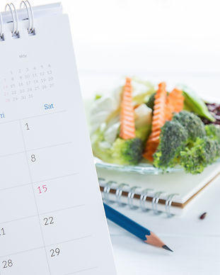 Calendar with notebook and vegetables on