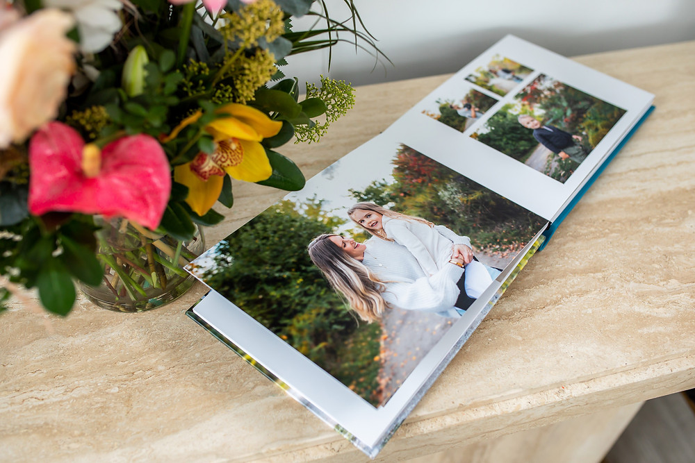 Open photo album with family images next to a flower bouquet
