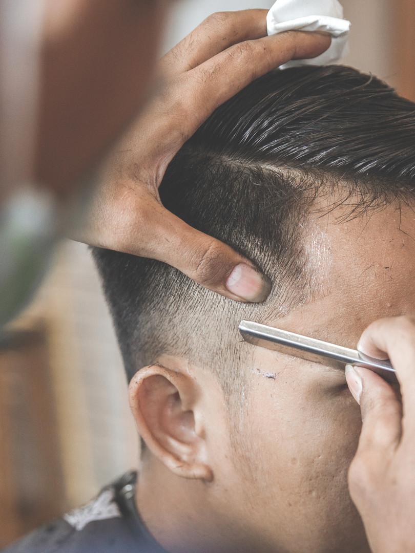 man getting his hair cut at barbershop.j