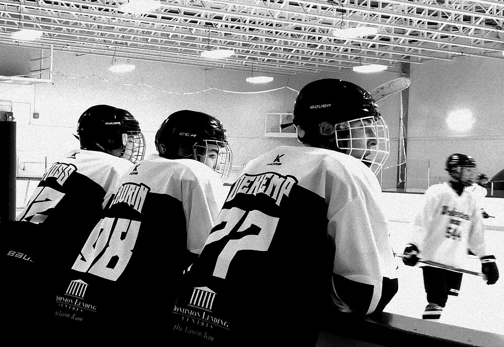 Three players on the bench watching the hockey game cheering on their team