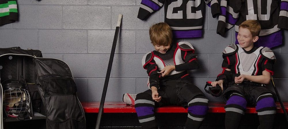 Two young hockey players getting ready as teammates in the locker change room.