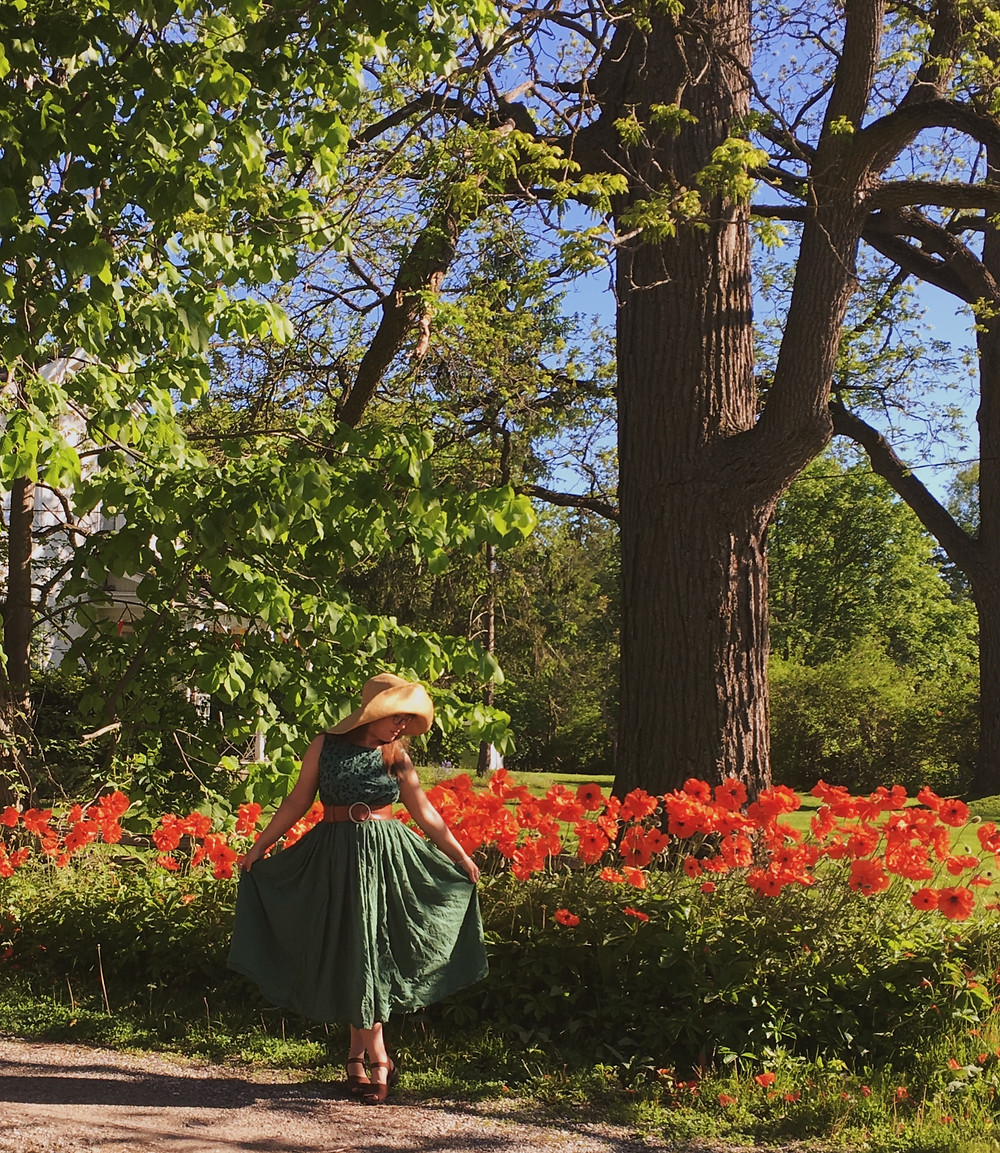 Terran stands in a green dress with a large sun hat in the sun, behind her a row of poppies stand nearly to her shoulders