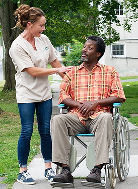 CCOR aide outside with a man in a wheelchair