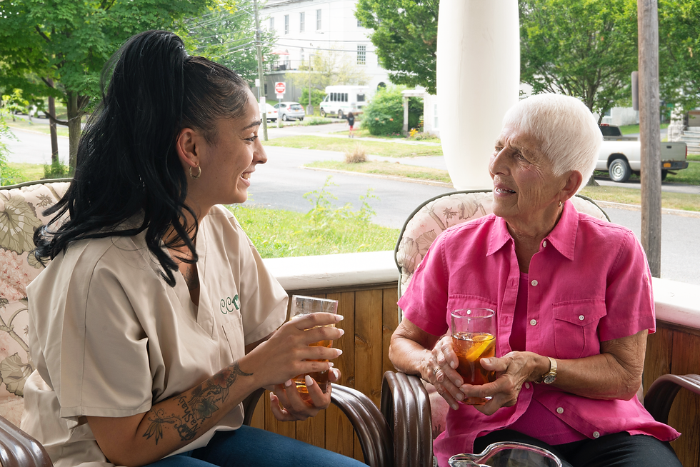 CCOR Aide and an elderly woman on a porch talking and sipping iced tea together.