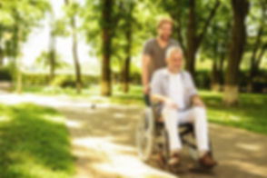 Caregiver pushing an older man in a wheelchair
