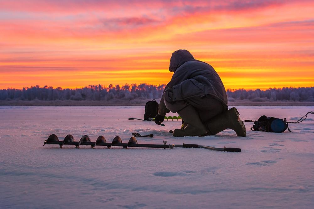 man ice fishing on lake minocqua