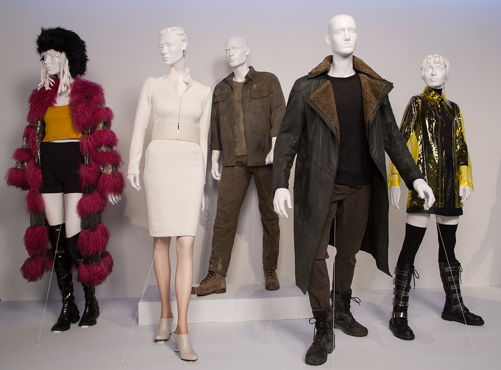 """Blade Runner 2049"" costumes by Renée April. L to R) Costumes worn by actors: Mackenzie Davis as Mariette, Sylvia Hoeks as Luv, Harrison Ford as Rick Deckard, Ryan Gosling as 'K', Ana de Armas as Joi"