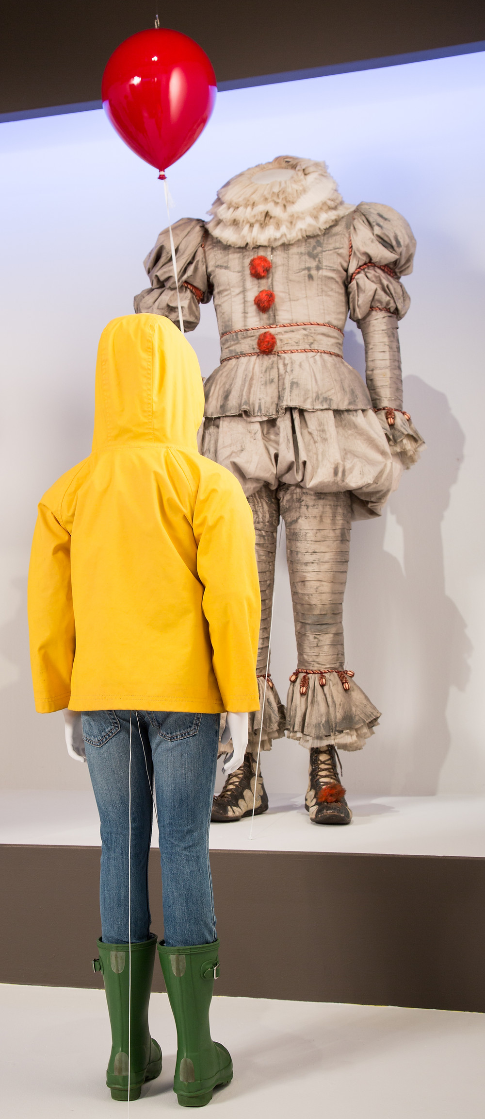 """It"" costumes by Janie Bryant. (L to R) Costumes worn by actors: Bill Skarsgård as Pennywise, Jackson Robert Scott as Georgie Denbrough"