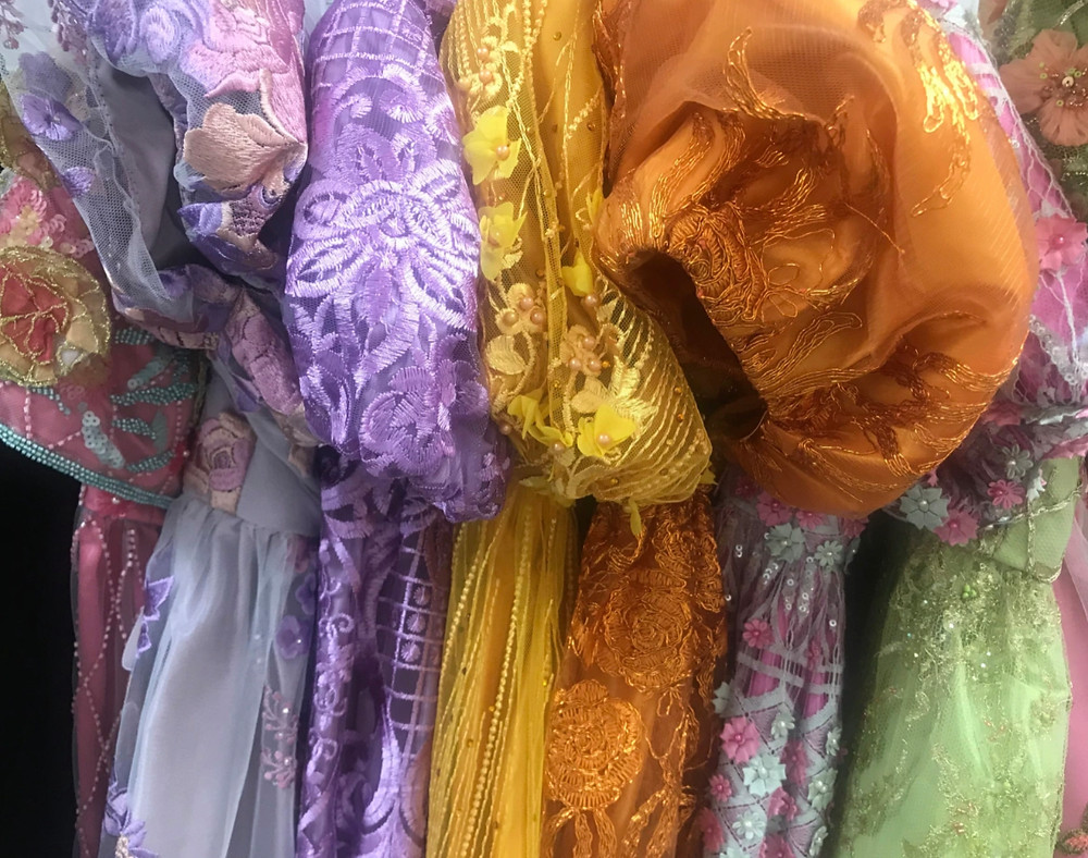 A selection of fabrics for the Bridgerton costumes hung up on a line.