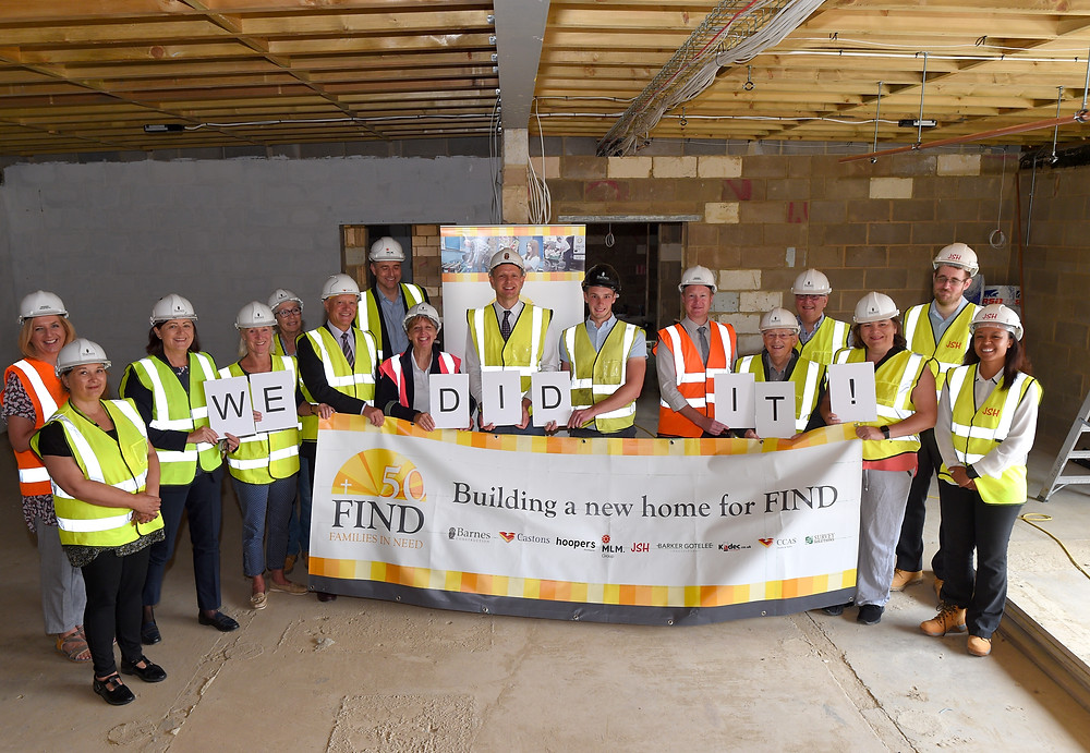 Maureen Reynel and the construction firms building the new food bank, holding a FIND banner and signs to say 'we did it!' to celebrate reaching the £100,000 FIND 50 lifeline appeal.