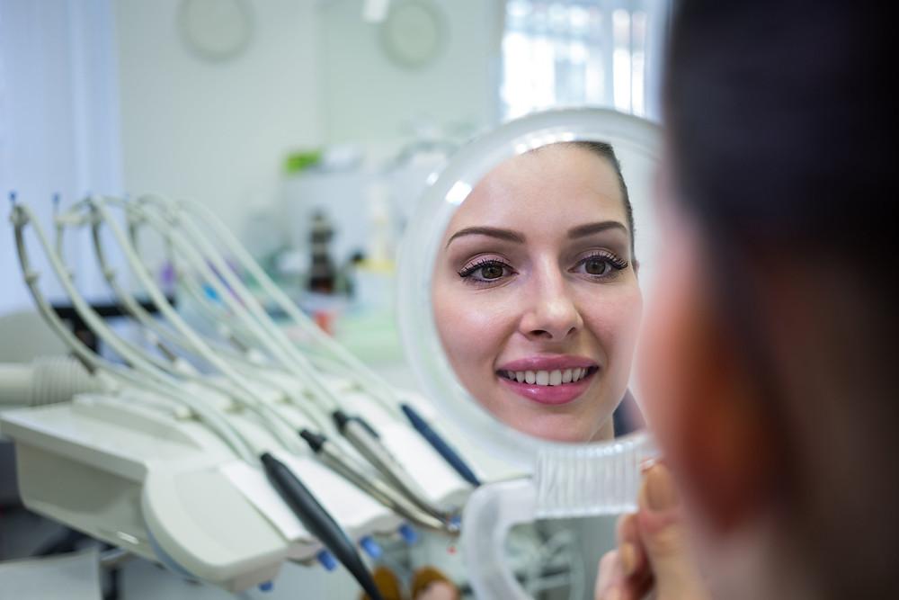 paciente no consultório odontológico olhando o sorriso em um espelho