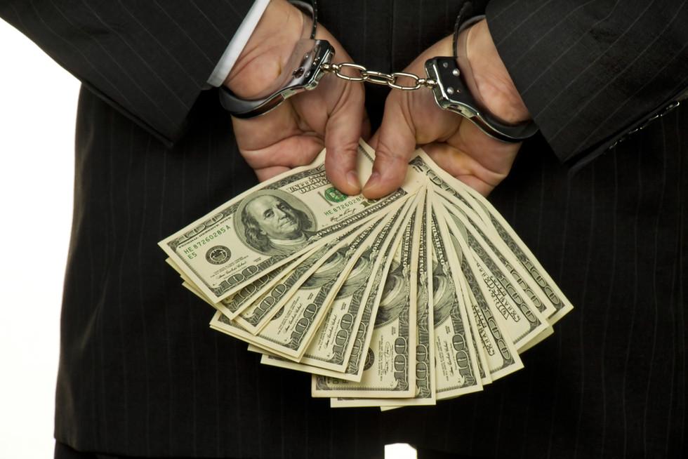 embezzlement_cuffedhands_money.jpg
