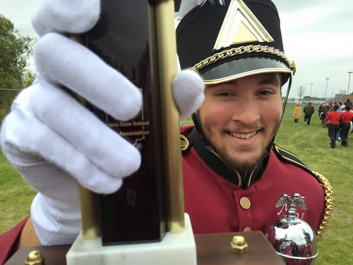 Lead Drum Major Tyler Bonds holding the Gold Trophy that the Marching Band won on October 3rd.