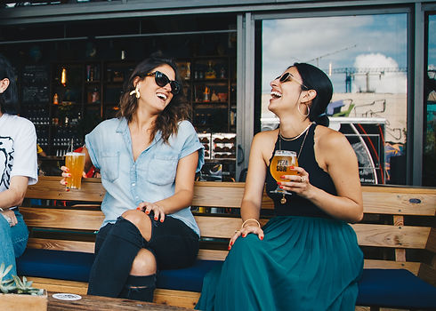 two-smiling-women-sitting-on-wooden-benc