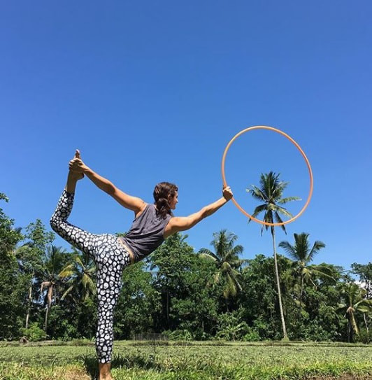 A picture about Lisa in a yoga pose holding a Hula Hoop in front of palm tree